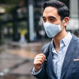 Businessman wearing mask in city