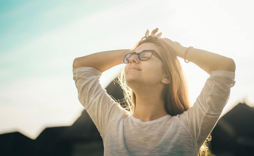 A woman breathing in outside.